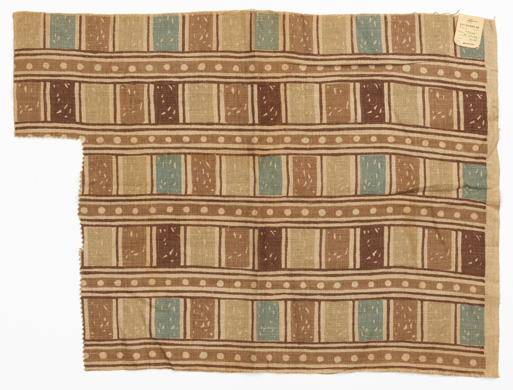 Length of printed fabric has a design of light brown horizontal stripes containing a row of white polka dots. In between stripes are rectangular compartments containing shades of brown and light blue.