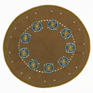 Round olive green tablecloth embroidered in a design stylized squarish flowers of blue, orange and yellow arranged in a circle. Ring of light yellow squares connects the flowers. Embroidered dashed lines in blue, light blue and brown form the outer ring along edge. Made from an embroidery kit. See 5896.111.2019.