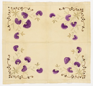 Off-white square tablecloth has in each corner a design of purple flowers with pale green stems and leaves. Flowers are made from embroidered knots. Each floral cluster enclosed by a brown and black scrolling border.
