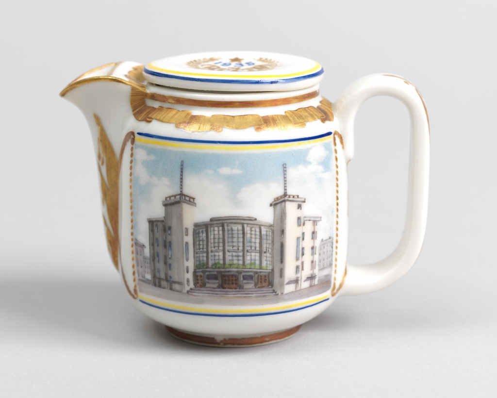 Cylindrical form (a), rounded at base and top, curved spout, wide loop handle, disk-shaped lid (b); painted in polychrome enamel on front with picture of the Gorky Palace of Culture and on back a griffin from Bankovsky Bridge in gilding; gilded ornament of ribbon border around top of body, flags along sides of spout, on handle; lid with a gilt emblem and the letters RSFSR, and the date 1935 in blue.