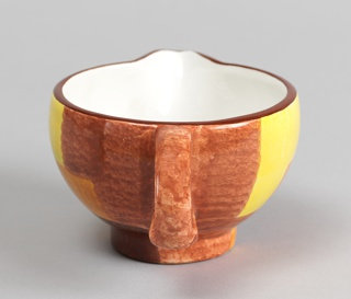 Hemispherical bowl with triangular spout, roughly D-shaped tab handle on side, and low cylindrical foot.  Mottled underglaze decoration of light brown field with geometric panels in yellow, orange and dark brown; dark brown band at mouth, white interior.