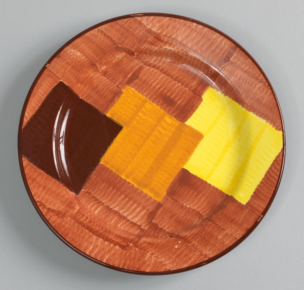 Circular form with narrow rim. Mottled underglaze decoration of light brown field with three overlapping squares in dark brown, orange, and yellow; thin dark brown band around rim.