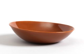 Shallow circular bowl flaring to a wide canted mouth. Rust colored glaze.