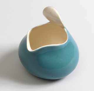 Bulbous body rising to wide mouth shaped to form spout and raised out-turned tab handle; glazed blue on exterior, white on interior.