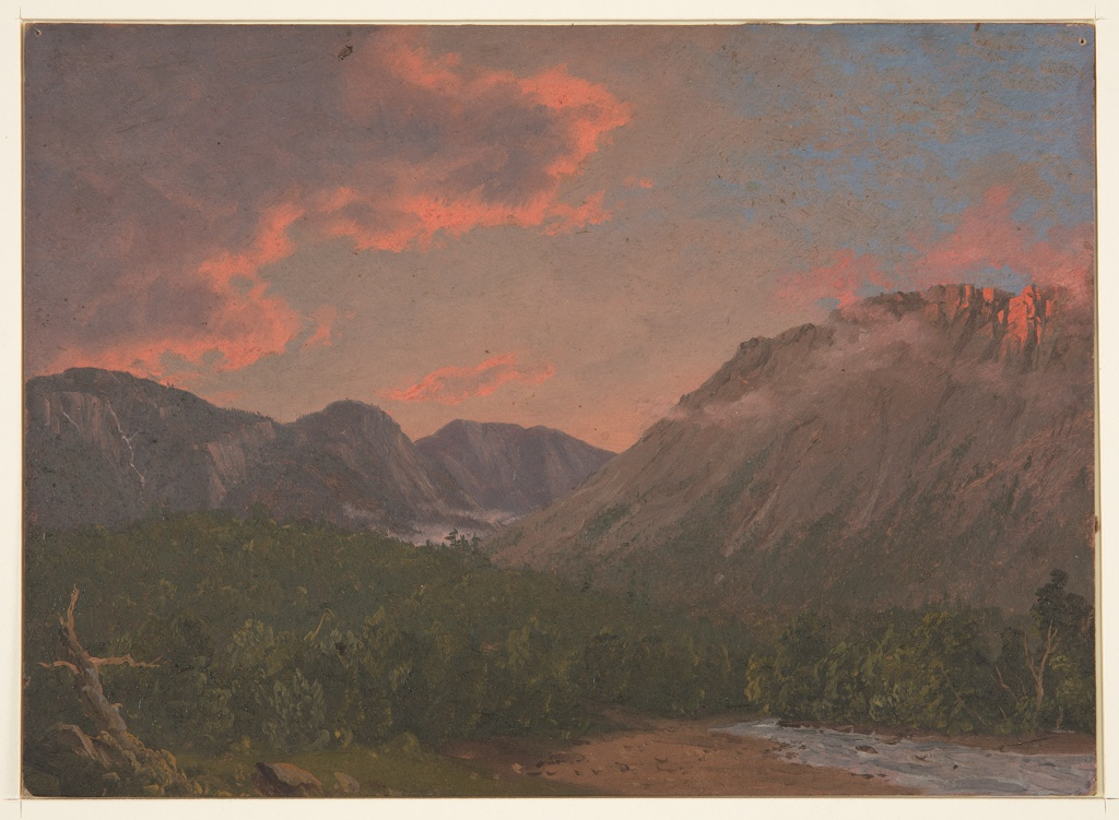 View into valley between mountains left and right.  A stream at lower right and low bishes and hill in forground.  Cloudy sky tinged red with blue patches at upper right.
