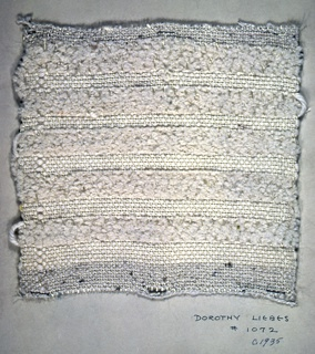 Woven sample mounted to a cardboard card with notations by the designer. Horizontal stripes of white on white textures. Warp is glossy white rayon yarn; weft alternates bands of white four-ply yarn in plain weave with bands of white chenille in 2/2 twill. Border of plain weave top and bottom; selvedges left and right.