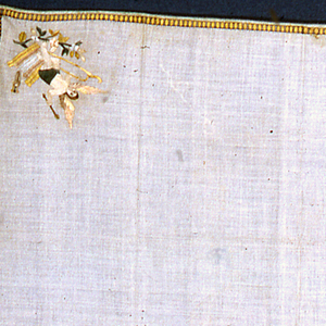 Square of off-white cotton embroidered with a narrow border on four sides, and a small scene in each corner: cupid holding a bow & arrow seated on a short column; two birds holding a bunch of flowers; a nude woman holding an arrow seated on a short column behind a flowering vine; landscape with a city and boats.