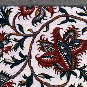 All-over floral vine pattern in black, two reds, blue and yellow on an ivory ground. Glazed.  Reproduction of 18th century style.