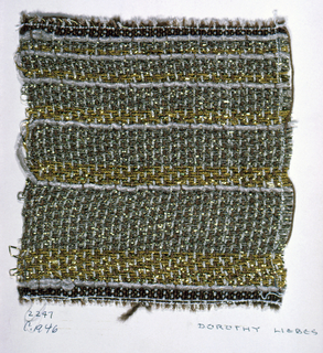 Twill weave in browns and gold. Warp alternates four-ply medium brown yarn, four-ply light brown yarn and wrapped metallic. Weft has bands of two-ply gold yarn paired with flat metallic gold; loosely plied green yarn paired with flat metallic gold; and one shot of chenille yarn in 3/1.