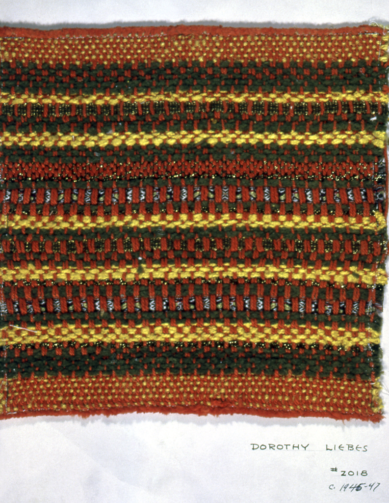 Striped sample with a warp of orange two-ply yarns, and a weft with bands of olive green chenille, bright yellow yarn, textured yarn, metallic threads, woven metallic and non-metallic tapes.