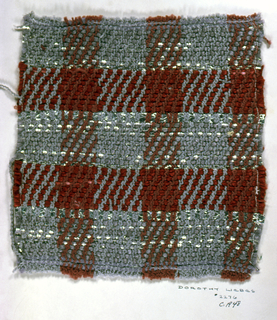 Sample of twill plaid in shades of dark red and gray. Warp has stripes of gray and dark red boucle yarn while the weft is comprised of smooth dark red yarn, smooth gray yarn, a wrapped silver yarn, flat silver yarn and silver braid.