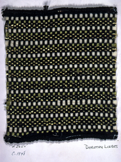 Plain weave sample with a warp of 3-ply black yarn. Weft is a repeating sequence of one green smooth yarn, one white fuzzy yarn, and three flat metallic paired with wrapped metallic yarn.