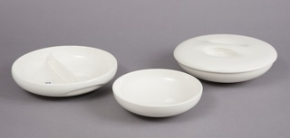 Three low white ceramic bowls, circular in shape: one large bowl with pinched sides and divided through its center cavity forming two compartments; one large bowl with smooth curved sides; one small bowl with curved smooth sides. One lid with pinched finger grips at top that fits on both large bowls. The forms are stackable: divided bowl with cover on top, large open bowl, small bowl.