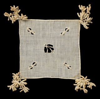 Square cover with small areas of cutwork and tassels on the corners.