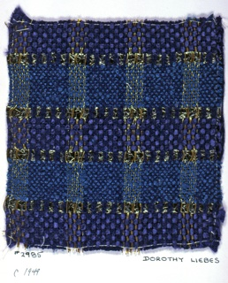 Plain weave plaid with paired and unpaired warps in shades of blue, gold and metallic gray. Warp is sixteen two-ply blue cotton yarns and eight wrapped metallic yarns alternating across the warp. Weft is a repeating unit of fourteen textured two-ply cotton turquoise yarn, one gray metallic braid, six blue synthetic yarns and one gray metallic braid.