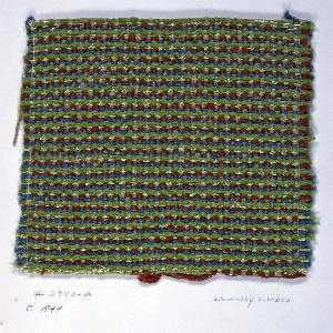 Plain weave with paired warps and textured yarns. Warp has paired warps of green two-ply yarn and brown two-ply yarn. Weft has a repeating sequence of blue textured yarn, red two-ply yarn, green boucle, and green chenille.