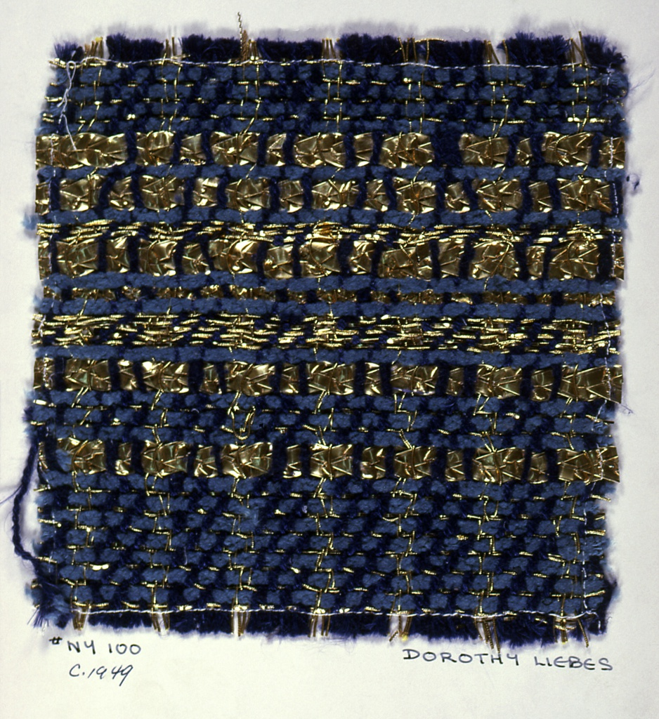 Twill of mixed cotton and synthetic yarns in shades of blue and metallic gold. Some sections are woven in 2/2 twill, some in 1/3 twill. Warp has stripes of eight bright blue yarns alternating with four wrapped metallic yarns. Weft is blue chenille alternating with three different metallic yarns. Sample is not large enough for a complete repeat.