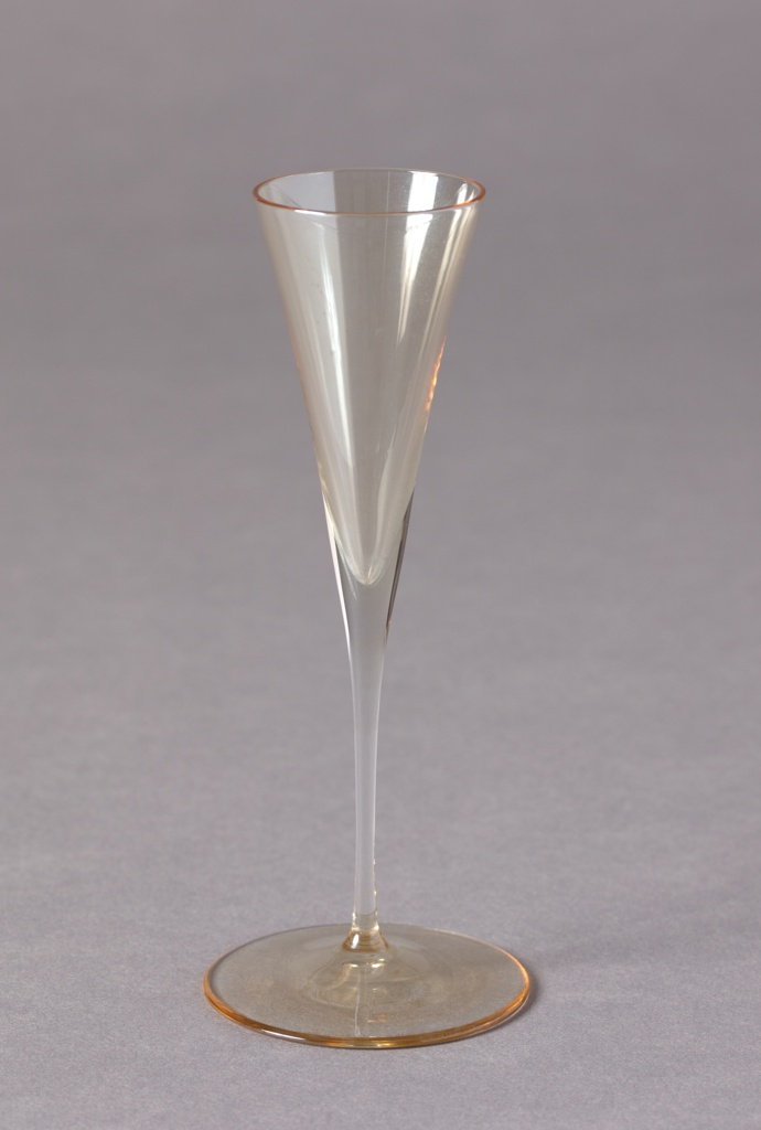 Clear, amber-toned glass decanter with long neck tapering to low body on thin stem terminating in circular foot;  liqueur glass-shaped stopper with ball-shaped knop. Three glasses, each of inverted conical form with a thin stem terminating in a circular foot.