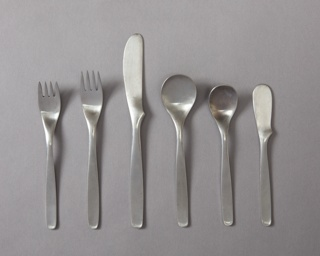 Six-piece place setting of two forks, knives, spoons, and one butter knife, each with a slightly tapering, curved handle with a rounded square terminal.