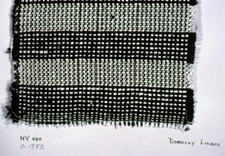 Plain weave with paired and unpaired warps in black and white. Warp has an alternating sequence of plied white synthetic yarn and four ends four-ply black yarn. Most of the fabric is woven with paired warps: two black, one black and one white, but there are three stripes where the four black yarns are woven singly. Weft has bands of white synthetic plied yarn and two-ply black yarn.