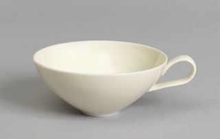 White circular cup with broad mouth, tapering to short circular foot; upturned loop handle on one side.