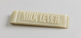 "Rectangular light gray plastic form, curved on left side, groove molded in right side; ""MILK LEVER"" molded in top."