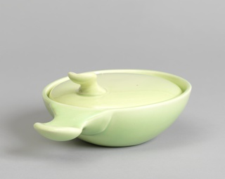 Chartreuse bowl (a) with angled circular mouth and curved tab handle at lower edge of mouth; slightly domed circular lid (b) inset in mouth of bowl, with raised and curved tab handle at one side. Interior glazed white.