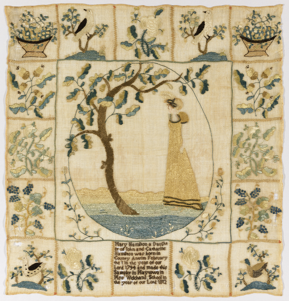 A central oval frame contains a scene of a woman facing a tree, the branches of which break out of the frame. The border is made up of squares containing motifs symmetrically arranged: grape vines, oak branches with acorns, birds in flowering trees, baskets of flowers, ducks in ponds, roses. The center square at the bottom contains the inscription: Mary Hamilton a Daughter of John and Catherine Hamilton was born in County Antrim February the 1 in the year of our Lord 1794 and made this Sampler in Maytown in Miss Welchens School in the year of our Lord 1812