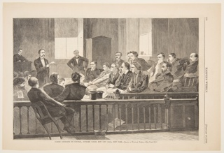 Jury seated in the jury box listening to a lawyer.