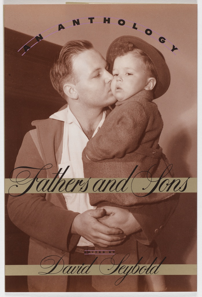 Front cover, sepia- colored photographic image of man holding and kissing a little boy on the cheek. Boy wears fedora, cordury pants, winter coat, and has left hand tucked in coat jacket. Two dark khaki-metallic colored horizontal bands superimposed over lower part of figures. Upper band contains the title in black cursive script, lower band contains author's name in cursive black script. Above figures' heads are two arc-shaped parallel lines with black text in between. Back cover, paragraph of book review in black. Spine, author's name and book title in cursive black letters.