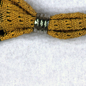 Miser's purse of netted black and yellow silk and finished at the ends with steel beads.