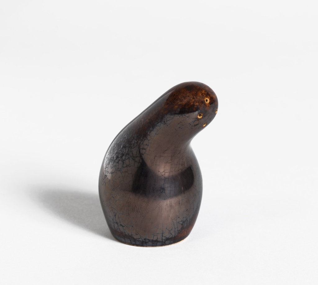 """Gourd-like form (a), having bulbous lower section tapering up to a curved neck; the rounded top with three holes set off-center; cork stopper (b) in underside. Lustrous """"Metallic Brown"""" glaze."""