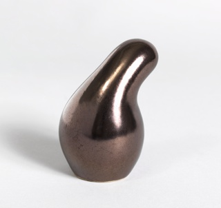 """Gourd-like form (a), having bulbous lower section tapering up to a curved neck; the rounded top with four holes set off-center; hole for cork stopper (b) in underside. Lustrous """"Metallic Brown"""" glaze. Cork stopper (b) has been pushed inside of shaker."""