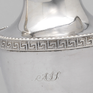 """Ovoid body with concave shoulder and neck, extended i- open spout.  Fret band and beading.  Scrolled handle.  Engraved on one side: """"Gussie from Father and Mother.""""  Monogram on opposite side: """"A J(?)S(?)."""" Photo'd 12/7/09."""