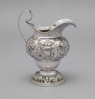 Part of repoussé and engraved tea set consisting of teapot (a), urn with lid (b,e), creamer (c), sugar bowl (d). Sloped gadroon runs