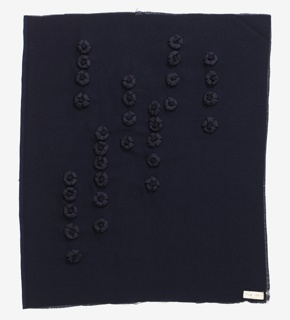 Panel of dark blue rayon crepe appliquéd with loops of ribbon in a design of rosettes.