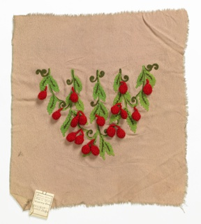 Sample of square beige fabric has a machine-embroidered design of leaves in two shades of green. Berries of red crochet hang from the leafy clusters.