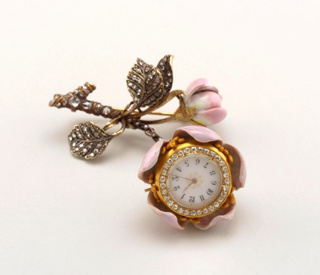 Chatelaine pendant watch forms the core of a pink wild rose, the stem and foliage of which are composed of enameled gold, studded with diamonds.