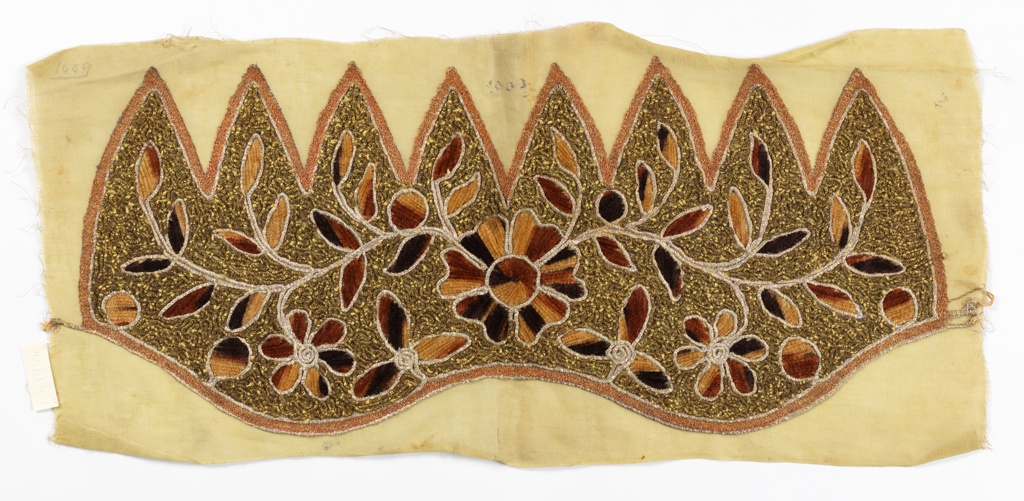 Panel embroidered to shape for a hat. Cream ground with floral scroll pattern in gradated shades of brown chenille, with couched green metallic wrapped yarns in vermicular pattern, metallic silver and copper outlines.