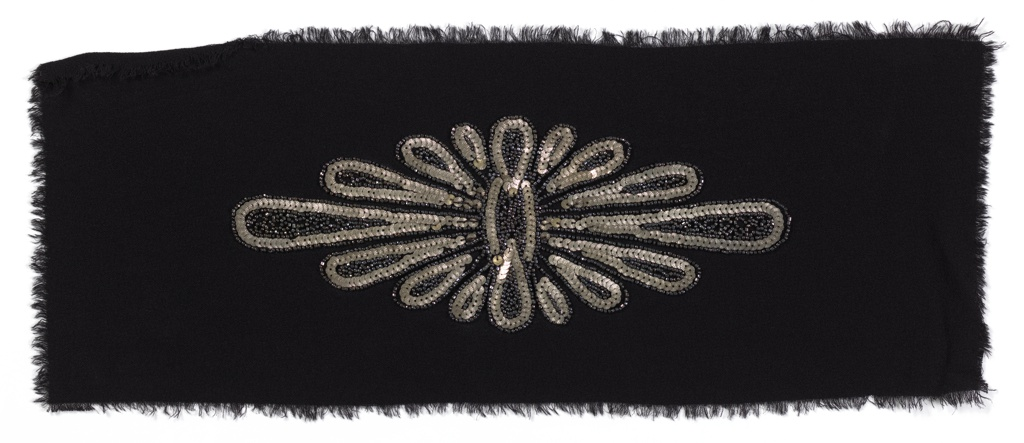 Oblong starburst motif done in silver embossed sequins and hematite seed beads, on black crepe ground. 1940s.