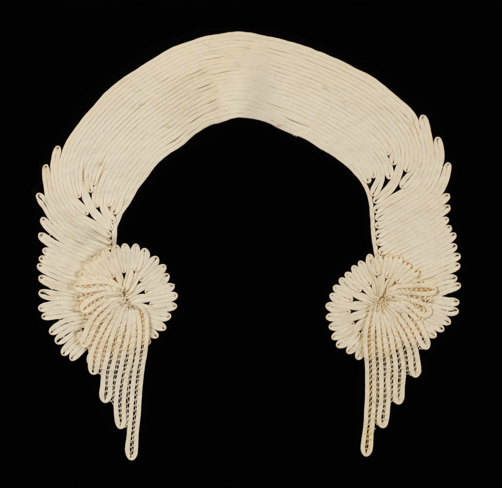 Passementerie for a collar. Fine white muslin ribbon strips, stitched together with an undulating pattern, with wing-shaped projections at each end with openwork bar accents.