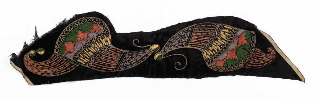"""Black velvet panel with """"cornucopia"""" type motifs, embroidered with chenille and yarn in shades of rust, yellow, green, and mauve, with metallic silver couched outlines and accents."""
