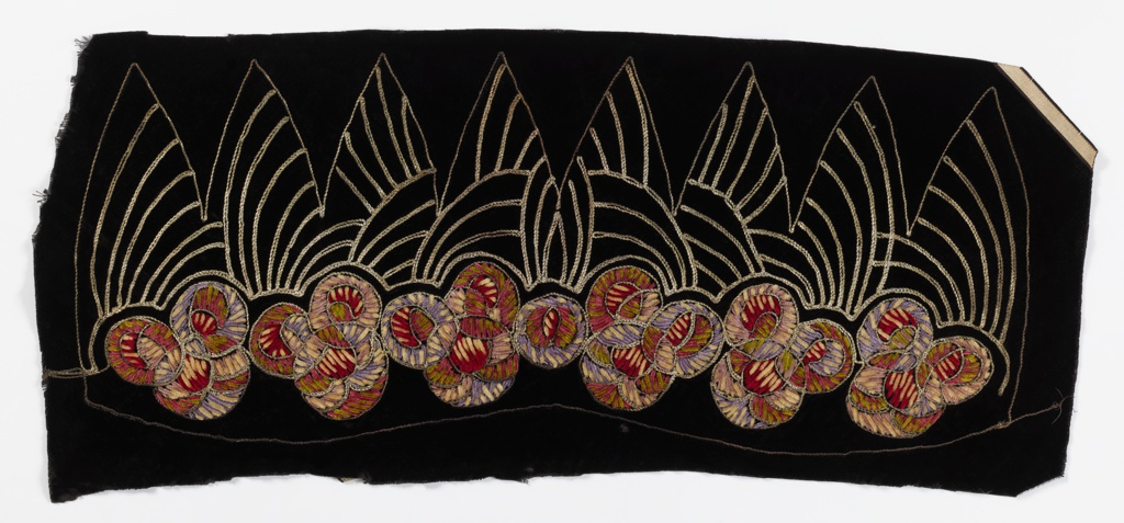 Panel embroidered to shape for a hat. Black velvet with chenille rosettes in shades of pink, purple, ivory and green, with metallic silver couched thread peaks and accents. Early 1930s.