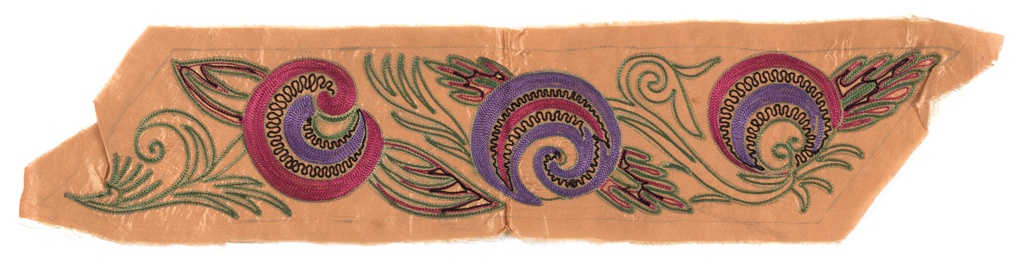 Band of copper colored acetate with purple, raspberry pink, green, and black chain stitched swirled rosettes and foliate motifs, accents in gold metallic chain stitch.