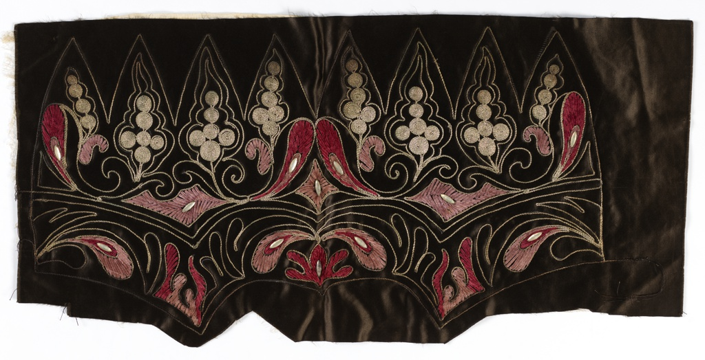 Panel embroidered to shape for a hat. Black silk satin with feather-like motifs embroidered in mauve and magenta chenille, silver metallic couched thread Asian-inspired motifs, and clear plastic gem accents.