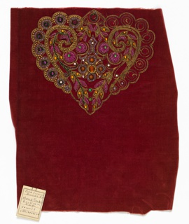 Red velvet fabric embroidered in a partially completed, heart-shaped motif worked in purple seed beads, gold bugle and round beads, green, orange and purple rhinestones and fuchsia colored metal thread in a boullion stitch.
