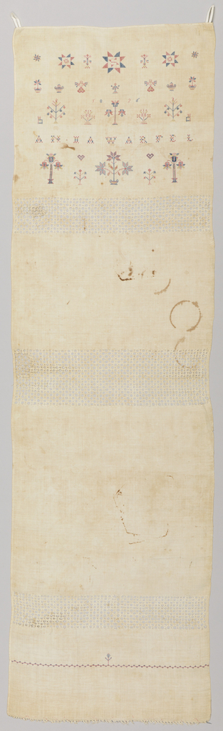 Long, narrow panel divided into four sections by three bands of withdrawn element work. In the top section, five rows of embroidery in red and blue threads show detached motifs of stars, flowering trees, chairs, hearts, etc., along with the name and date; the other three sections are unadorned.