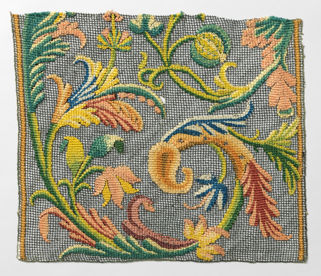 Portion of a large scale, multicolored floral design on green knotted net.