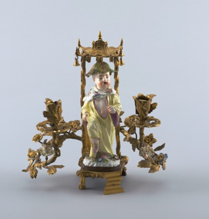 Porcelain Chinoiserie figure of a young boy dressed in a yellow robe with flowered shawl, wearing a leaf cap and pink slippers, prancing beneath an ormolu bell-hung canopy on rustic supports; the base fitted with two scrolling enleafed candle arms bearing porcelain flowers.