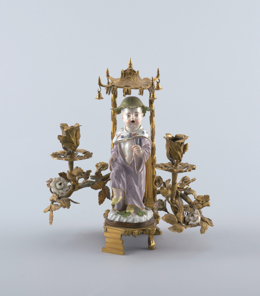 Porcelain Chinoiserie figure of a young boy dressed in a lavender robe with flowered shawl, wearing a leaf cap and yellow slippers, prancing beneath an ormolu bell-hung canopy on rustic supports; the base fitted with two scrolling enleafed candle arms bearing porcelain flowers.